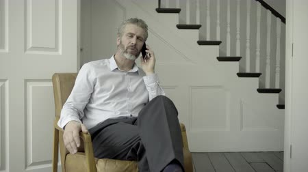affluent : Mature Adult Male working from home on the phone Stock Footage