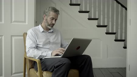 affluent : Mature Adult Male working from home on laptop Stock Footage