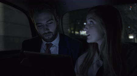etnisite : Business people in taxi using digital tablet