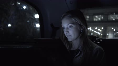 black cab : Young adult female in taxi using digital tablet at night