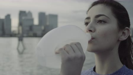 tamisa : Female runner drinking water by river Thames, London