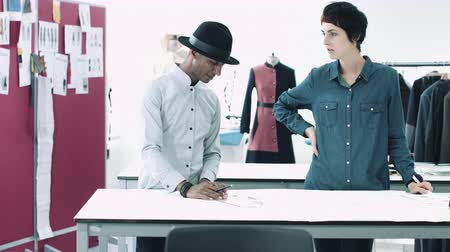 dressmakers model : Fashion designers looking at digital tablet and clothes in studio Stock Footage