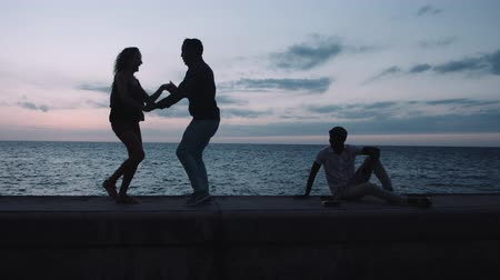 sky only : Man and woman enjoying salsa dance on retaining wall at sunset, sea in background Stock Footage