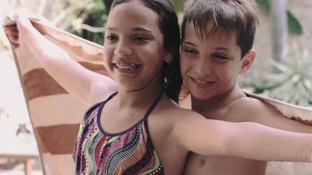 children only : Sibling wrapped in towel and enjoying near swimming pool