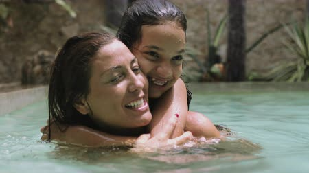 anne : Daughter embracing and kissing to her mother in swimming pool Stok Video
