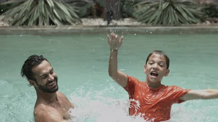 pai : Man throwing his son while enjoying in swimming pool