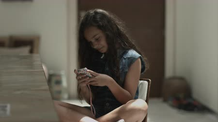 kolsuz : Girl sitting on chair and playing with mobile phone Stok Video