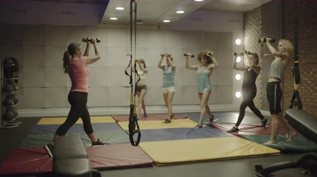 empurrando : Group of adult women exercising with weights in gym