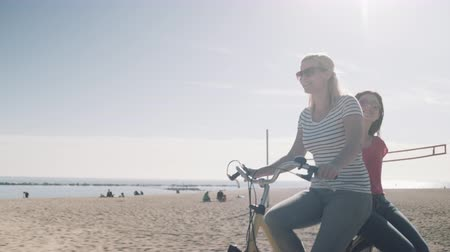 vacation : Young Adult Tourists cycling on beach in summer Stock Footage