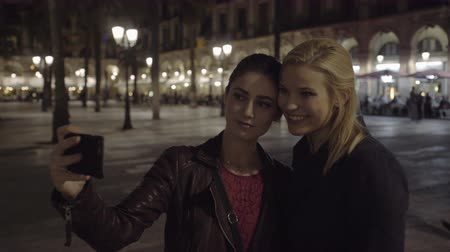 hostující : Young Adult Women at night visiting square in Barcelona and take selfie Dostupné videozáznamy
