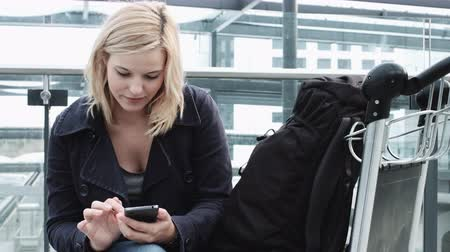 trolley : Young Adult Female on smart phone and waiting in airport