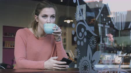 contemplativo : Young adult woman looking at smart phone in cafe