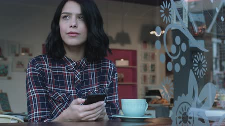contemplative : Young adult woman looking at smart phone in caf+0Aw9AKk- Stock Footage