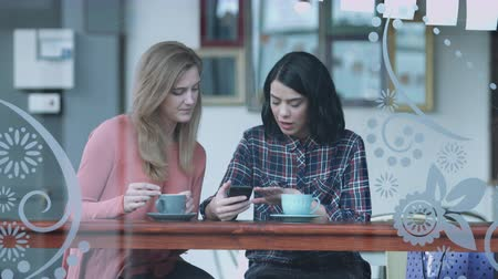 блюдце : Female friends in coffee shop looking at smart phone