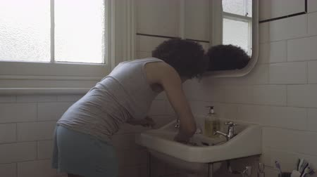 afro amerikan : Afro American Woman in bathroom brushing teeth Stok Video