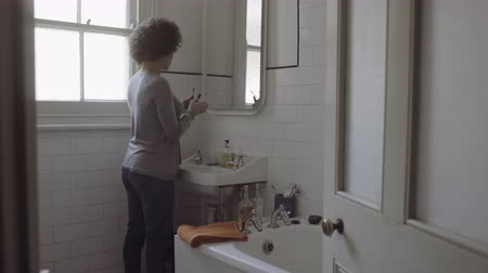 pia : Afro American Woman in bathroom doing make+AC0-up in mirror Vídeos