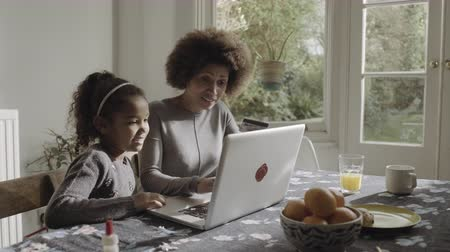 puericultura : Mother with daughter teaching on laptop in kitchen