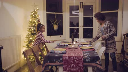 christmas tree with lights : Mother and daughter prepare Christmas dinner table