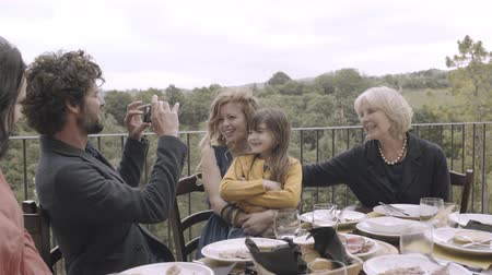 Father taking picture of family meal