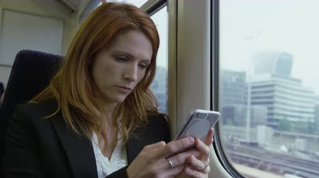 Commuter on her way to work looking out of the window and using smart phone