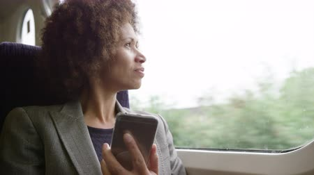 call out : Afro American commuter on her way to work looking at smart phone
