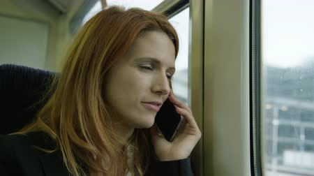 call out : Commuter on her way to work looking out of the window and using smart phone