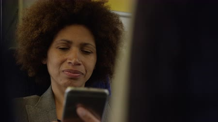 Afro American commuter on her way to work looking at smart phone