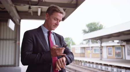 Businessman waiting for delayed train on platform Stok Video