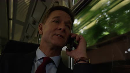 call out : Businessman on train on his commute talking on smart phone Stock Footage