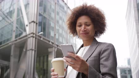 навынос : Afro American businesswoman in city using smart phone with takeaway coffee