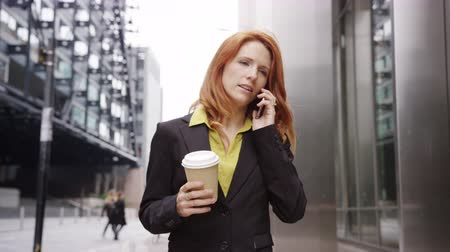 Businesswoman in city using smart phone with takeaway coffee Stock mozgókép