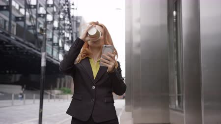 Businesswoman in city using smart phone with takeaway coffee Stok Video