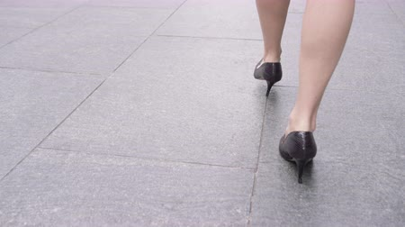 career path : Close up businesswoman feet in heels walking down pavement in city to work