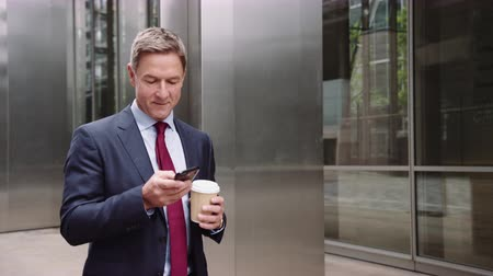 Businessman walking to work using smart phone with takeaway coffee Stok Video