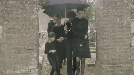 loved : Mourners leaving graveyard in the rain