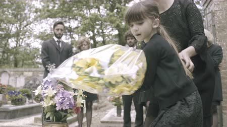 loved : Mother and Daughter laying flowers on grave