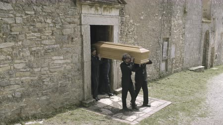 Pallbearers leaving Church with coffin followed by family Stok Video