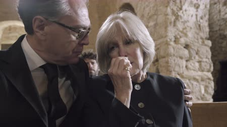 parentes : Grandmother crying at a funeral with granddaughter