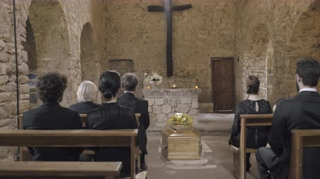 trumna : Mourners at funeral service in church