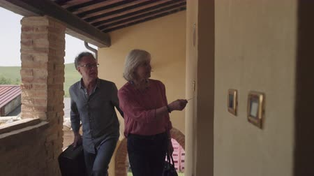 Senior couple arriving at holiday apartment
