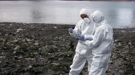 environmentalist : Forensic scientist examining sample at river bank