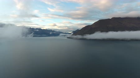 yeni zelanda : New Zeland High Fly Through Clouds Over Lake Towards Mountains at Sun Set