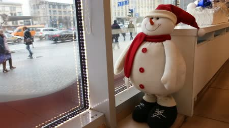 estilização : Funny toy snowman looks from the cafe to the street, watching the passers-by Vídeos