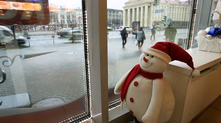stylization : Funny toy snowman looks from the cafe to the street, watching the passers-by Stock Footage