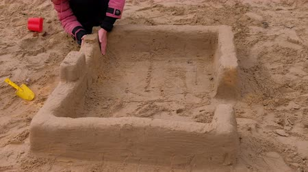 patting : Girl playing with sand on the yard. Construction of a sand castle