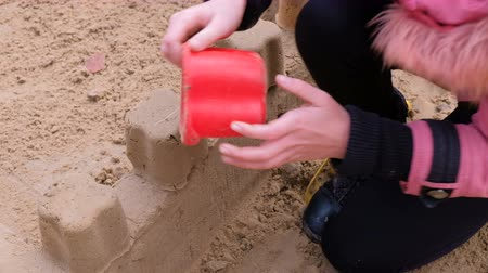 stavitel : Girl playing with sand on the yard. Construction of a sand castle