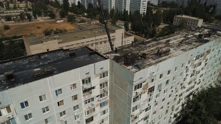 ремонт : Description: Workers clean the roof of a multi-storey building from an old roofing felt. Repairing or re-roofing. Birds eye Aerial view. 4k video