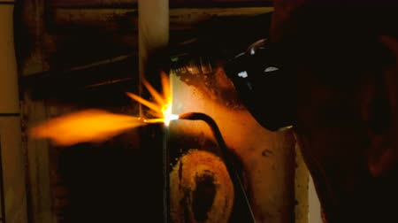 inverted : The welder welds the pipe. The man is doing his job