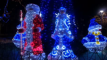 The Santa Claus, Snow-maiden, snowman, near with decorated Christmas tree