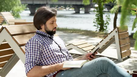 özenli : Guy is sitting on bench and reading a book. Then he got message on phone. Man is taking it and looking at phone and smiling. He is typings message. Then he put off phone and continue read book again.